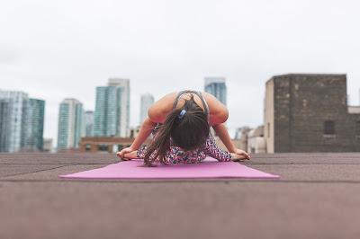Mujer practicando yoga en una terraza urbana