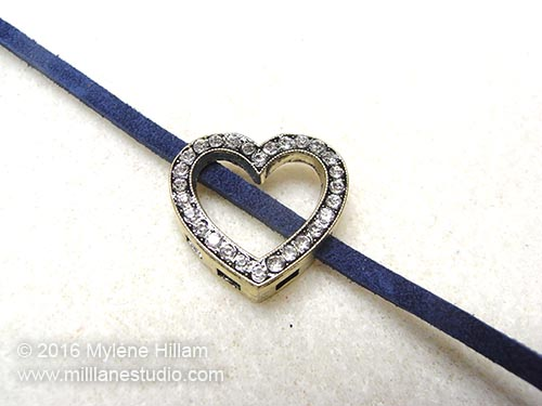 Cadet Blue leather lace is strung the the heart slider diagonally.