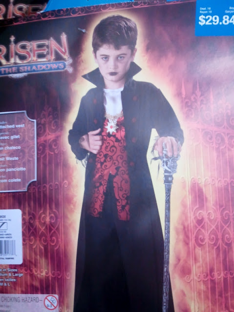Photo of a male child in dark lipstick wearing embroidered 'vampire' costume and holding a cane.