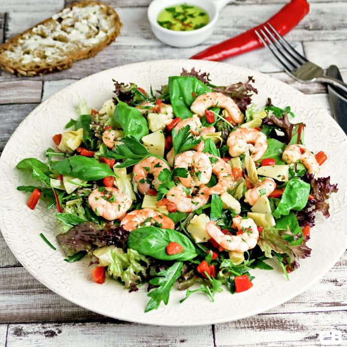 Salade van gemarineerde grote garnalen, artisjokkenharten en kruidensla