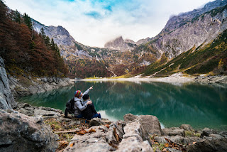 Two people sat beside a lake in forested mountainous terrain. One points out something to the other.