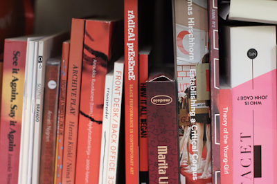 An image of art-related books ordered by color (red)