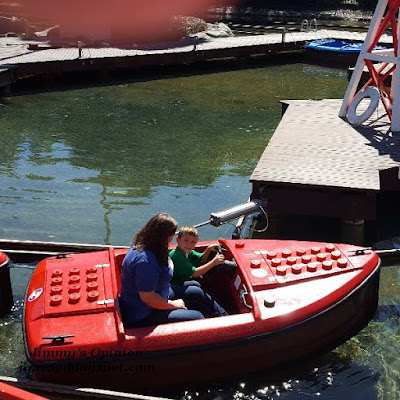 Our grandson Benjamin driving a red boat taking his mom for a ride at Legoland.