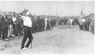Black and white photo of a man in white polo shirt and black pants throwing a cricket ball while other players in white clothing stand to hit the ball. The cricket players are surrounded by men in various clothing, some wearing military uniform and others wearing suits.