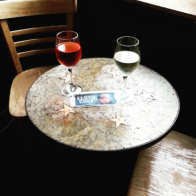 Two glasses of wine on a cafe table with a ticket to a Lloyd Cole concert between them.