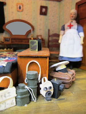 One-twelfth scale miniature bedroom scene with a nurse in the background, and a pile of luggage including a gas mask and military items in the front.