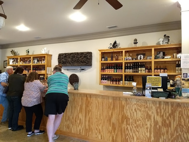 Wine tasting room with a long wooden counter top and several people tasting wine