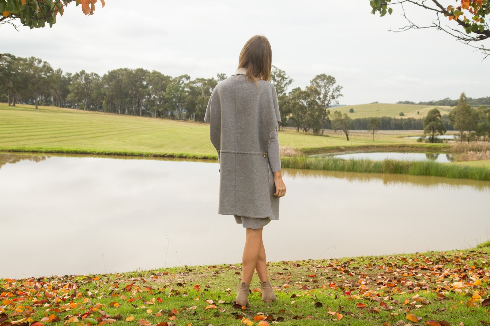 Fashion and travel blogger, Alison Hutchinson, is wearing a grey sweater dress and long wool vest for a day of wine tasting in the Hunter Valley