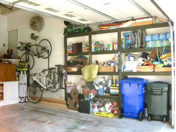 messy shelves in the garage. with bikes on the wall.