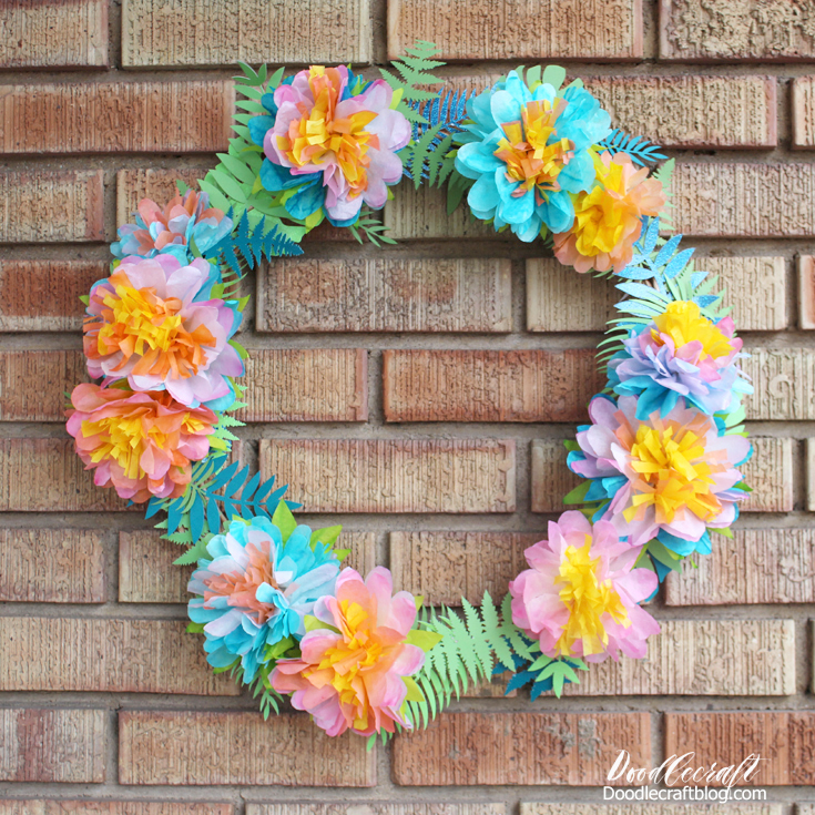 Tropical paper fronds decorating a wreath with coffee filter flowers