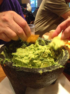 Bowl of guacamole with people dipping