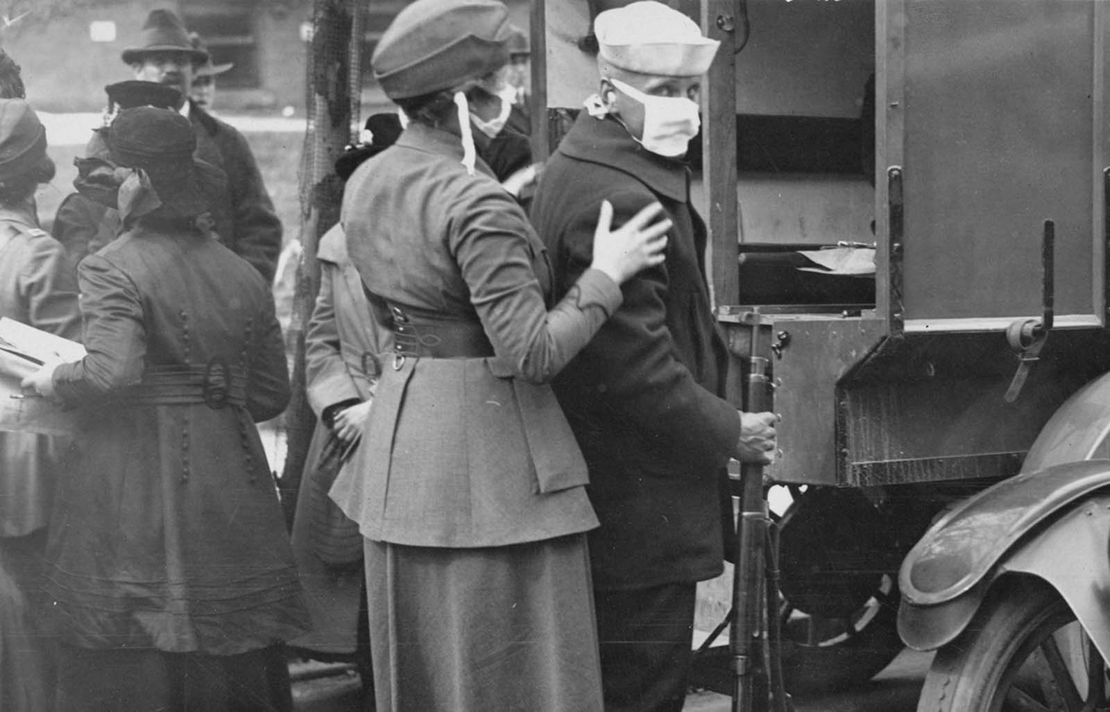 A sailor and a member of the Women's Motor Corps wear masks while treating influenza patients injured by the explosions of a coal loading plant at Morgan, New Jersey, on October 5, 1918.