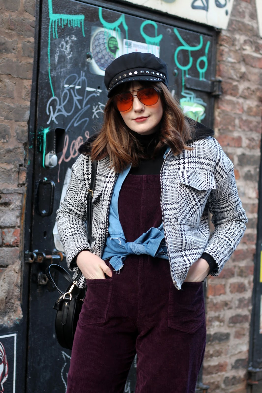 dungarees seventies style fashion with baker boy cap, aviator sunglasses, check jacket and Burgundy cord dungarees