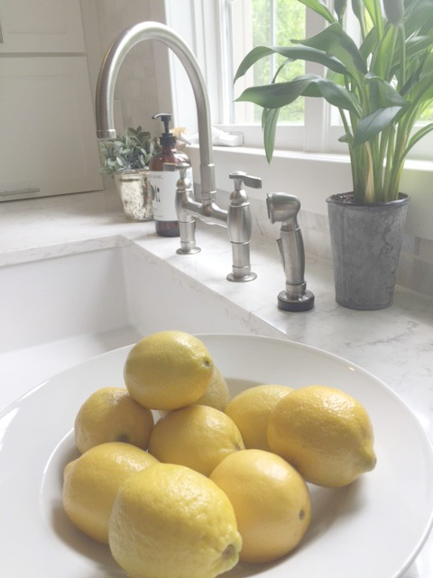Lemons in a white bowl on a Viatera Minuet countertop in kitchen near farm sink - Hello Lovely Studio.
