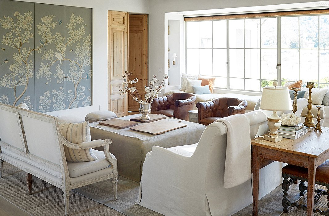 Elegant modern farmhouse living room at Patina Farm with rustic tables, Gracie wallcovering, linen, and antiques (found on Hello Lovely)