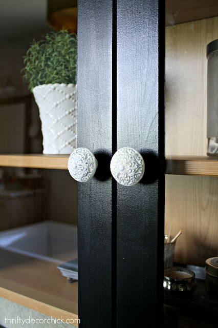 White knobs on black cabinet doors