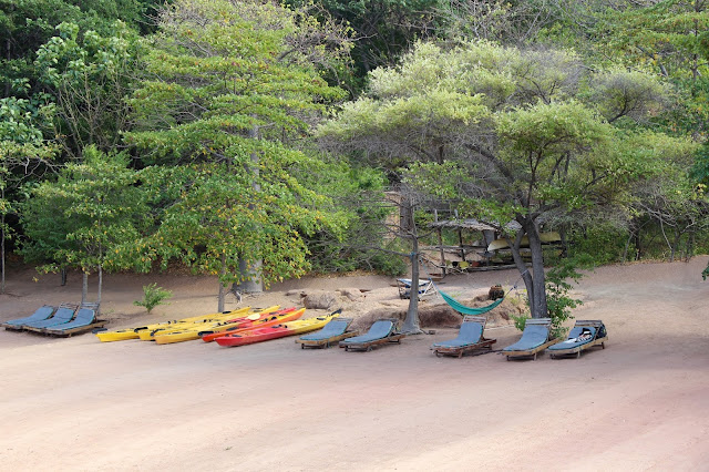 Sun loungers and kayaks on the main beach at Mumbo Island