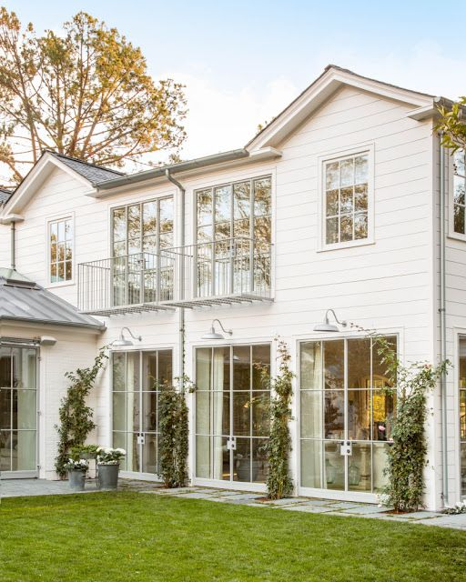 White modern farmhouse exterior with steel windows by Giannetti Home