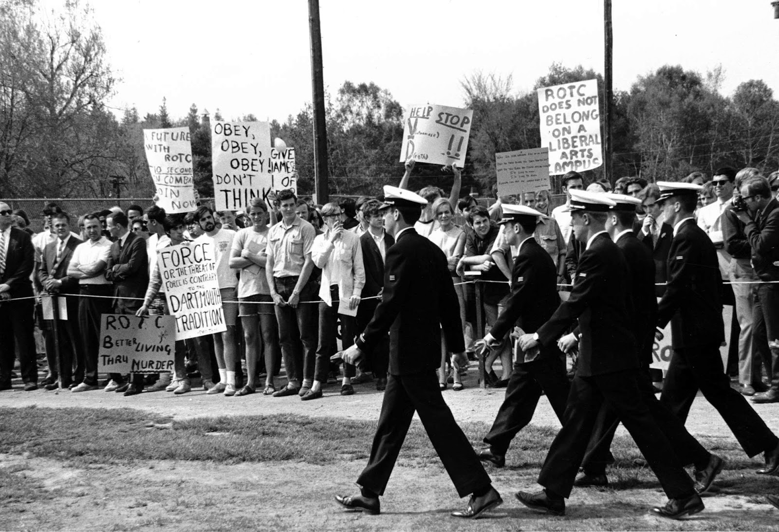 A photograph of a small group of men in uniform walking past a protest.