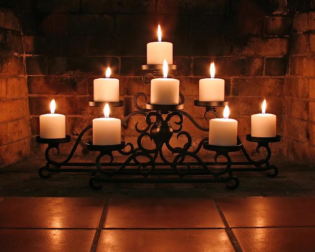 Afbeelding met kaarsen onder de schoorsteen