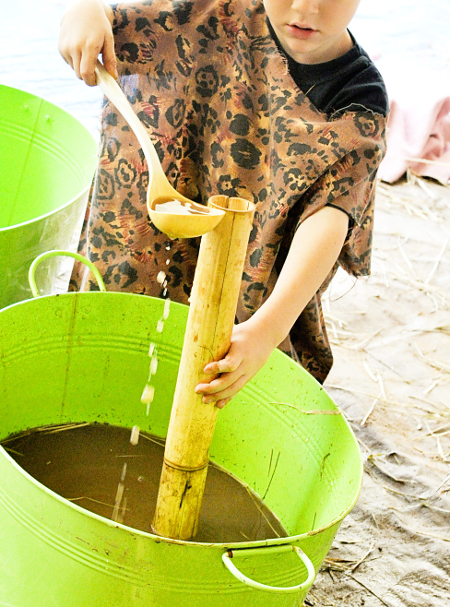 Picture of a child playing with muddy water used to make mud bricks.