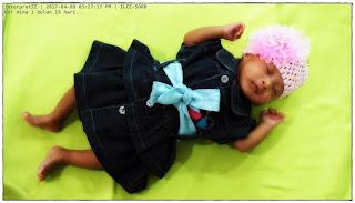 gambar bayi Nor Aina dipakaikan gaun denim biru dan headband pink