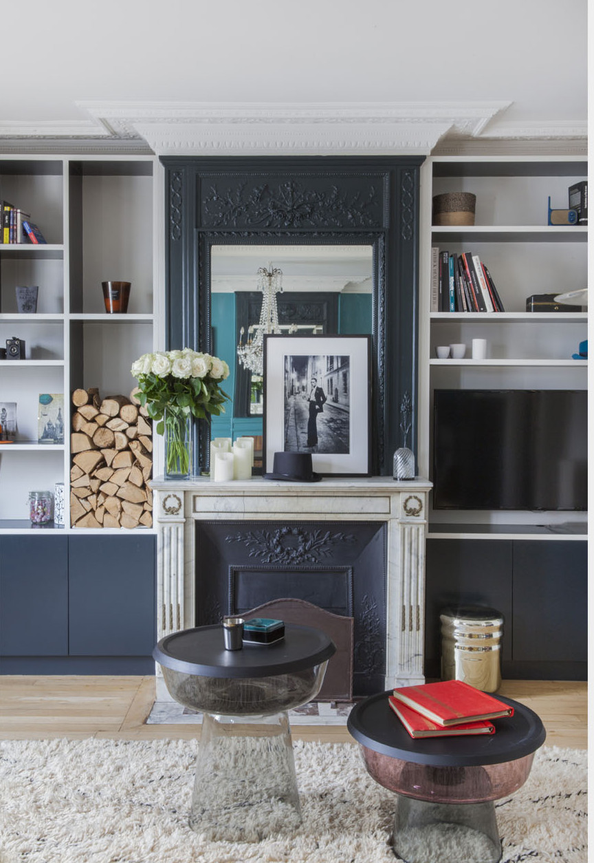 paris apartment with teal color, mid century modern furniture, bookshelf, fireplace
