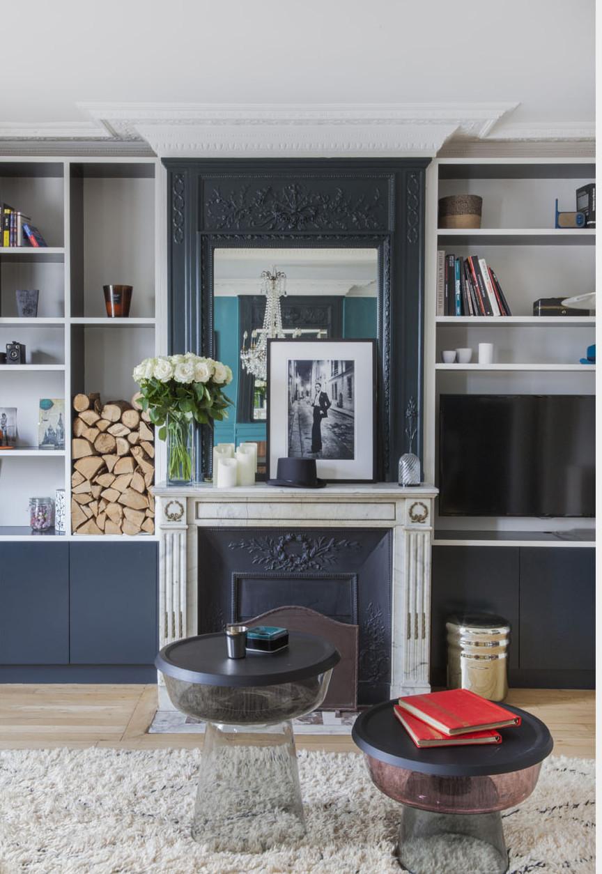 paris apartment with teal color, mid century modern furniture, bookshelf, fireplace