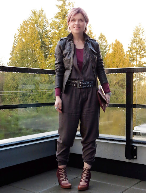 "styling a ""utility"" jumpsuit over a long-sleeved tee, with an envelope clutch, moto jacket, and lace-up heels"