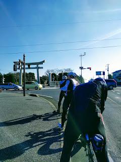 左手に鳥居が見える交差点前で信号待ちする自転車乗りメンバー達の後姿