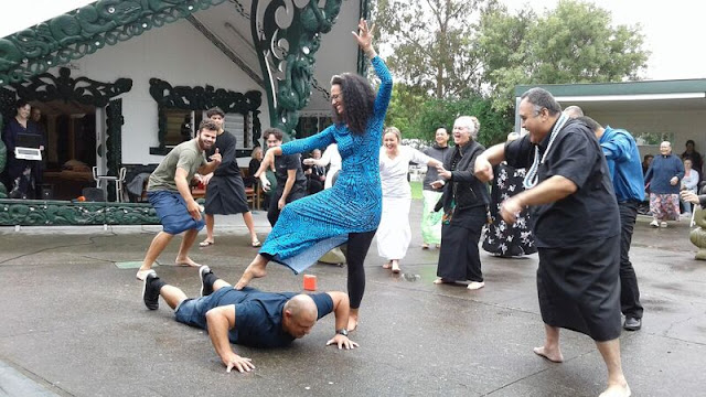 Selina performing her Siva dance with the help of her family, including husband Dave, underfoot.