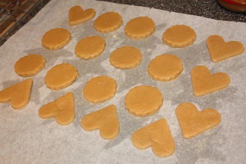 cut out sugar cookie dough on a baking sheet, in heart and circle shapes