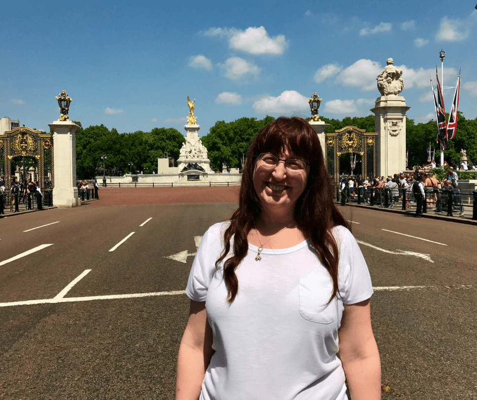 Woman standing in front of monument in front of Buckingham Palace.