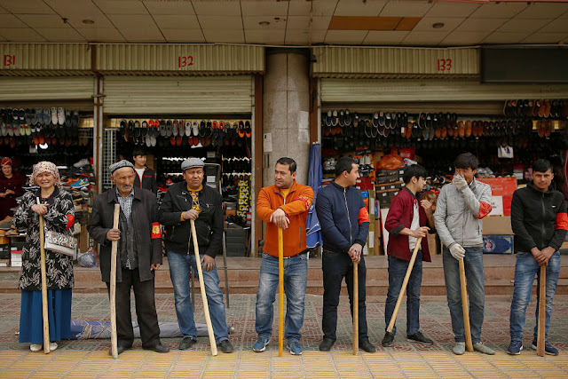 Image Attribute: Shopkeepers line up with wooden clubs to perform their daily anti-terror drill outside the bazaar in Kashgar, Xinjiang Uighur Autonomous Region, China, March 24, 2017. REUTERS/Thomas Peter