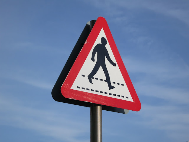 Triangular sign with red borders to say pedestrians may walk this path.