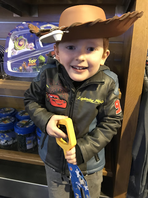 Little boy standing in Disney shop with merchandise in the background, wearing a cowboy hat and holding a grabber toy