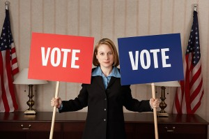 "photo of woman holding ""vote"" signs"