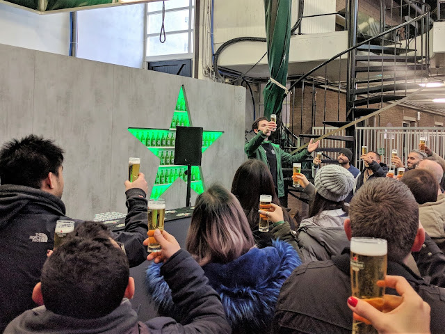Lots of people Toasting with beer at Heineken Experience