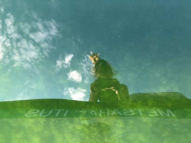 Metsähallituksen veneen ja kuvaajan heijastus vedenpinnalla.