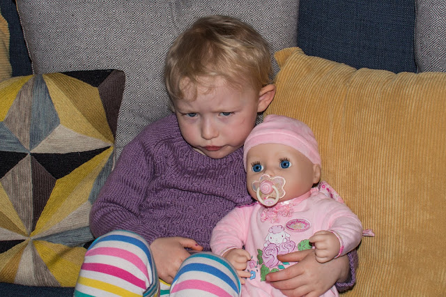 Toddler cuddling baby annabell while reviewing her