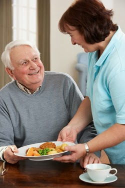 Elderly man taking meal from care assistant