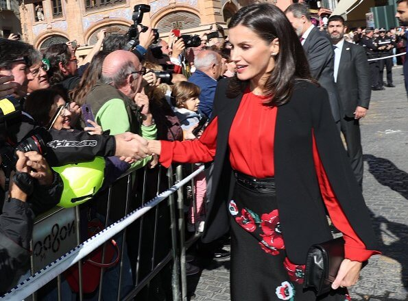 Queen Letizia wore Zara cape style jacket in black and Hugo Boss Banora gathered silk blouse in red. diamond earrings