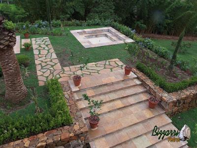 Execução do caminho no jardim com pedra Goiás tipo cacão com juntas de grama, das escadas de pedra Goiás serrada, dos bancos de pedra na praça da fogueira com o piso de pedrisco palha em sítio em Piracaia-SP.