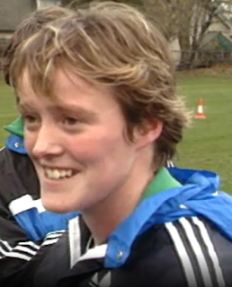 head and shoulders of a smiling woman with light, short hair in a field wearing a black and blue jacket