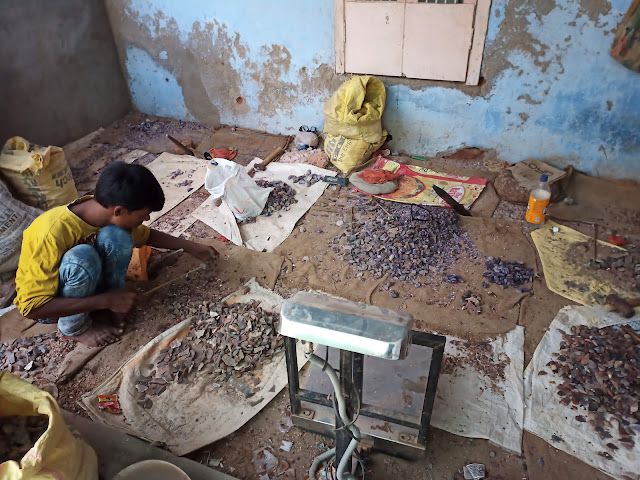 Man crouching while working in bead workshop
