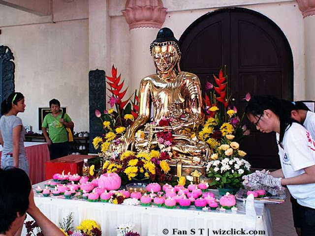 A golden Buddha statue at the front of Asokan hall