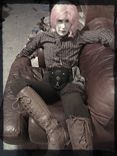 Androgynous steampunk with shironuri white face, pastel pink hair, stripped shirt, brown pants, and brown boots.  Person is lounging on a sofa.