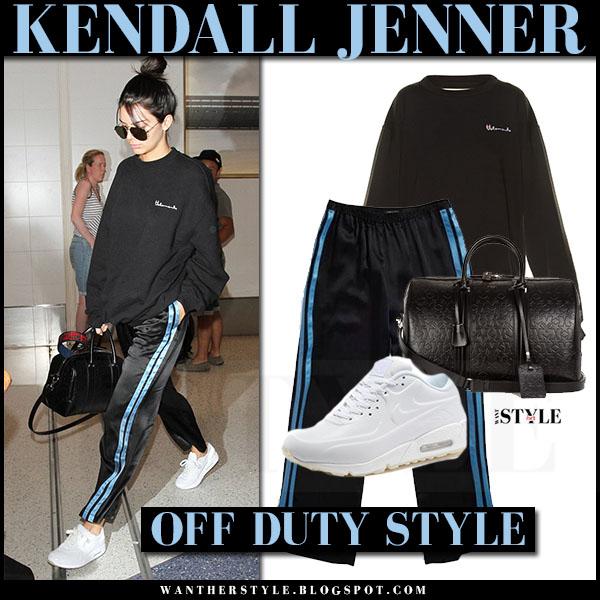 Kendall Jenner in black sweatshirt, black side stripe pants and white sneakers