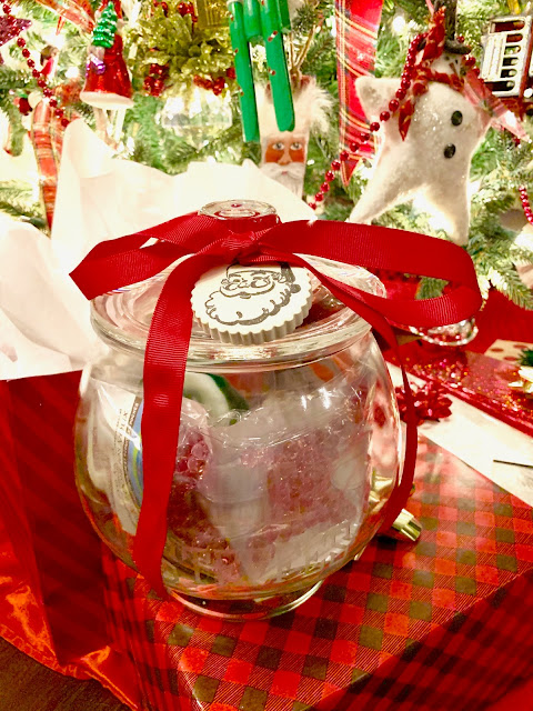 Glass jar filled with spa items under a decorated Christmas tree