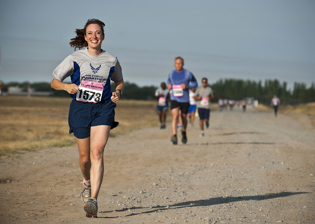 Woman running on dirt path, smiling and happy